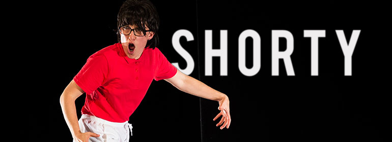 Hester Chillingworth as Shorty dressed in a black wig, glasses, red shirt and white shorts
