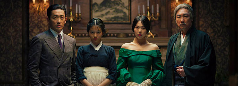 four people in suits and dresses in a stately looking house in the film The Handmaiden