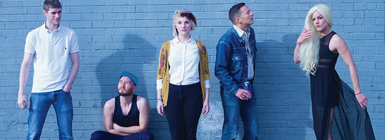 A lineup of actors in Queers against a blue brick wall from the Dublin International Gay Theatre Festival 2017