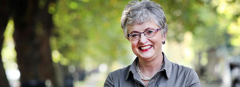 Minister Katherine Zappone, who is launching the LGBT youth strategy questionnaire, smiling in front of foliage