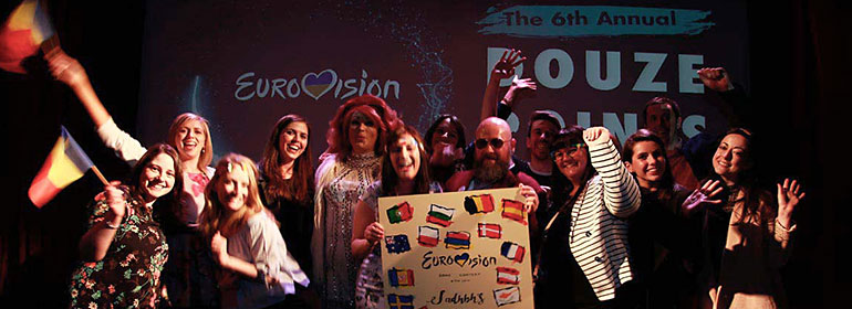 people on stage at GCN's Eurovision Douze Points Party 2017 holding a eurovision sign and waving flags