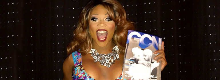 Peppermint holding a copy of GCN with the marriage equality mural on the cover of it