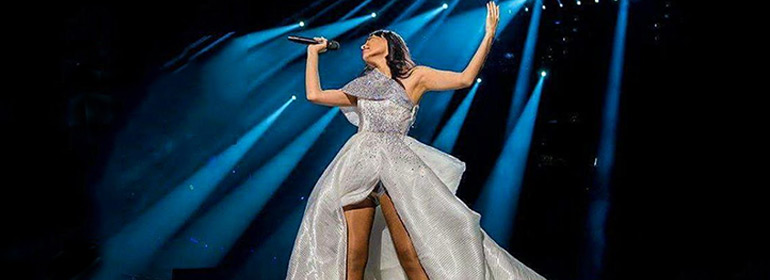 A Eurovision Song Contestant wearing a gorgeous silver dress which could be a costume idea to wear to GCN's Eurovision Douze Points Party