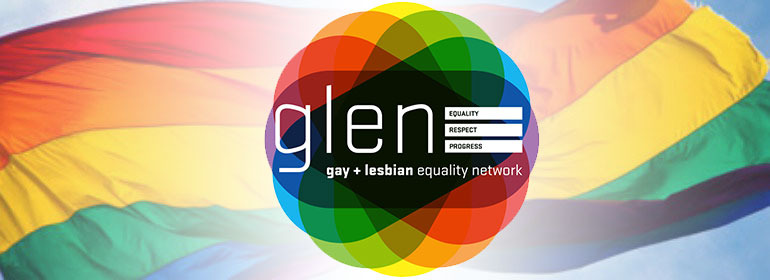 A Rainbow Flag behind the rainbow coloured GLEN logo the gay and lesbian equality network of ireland which just announced its closure