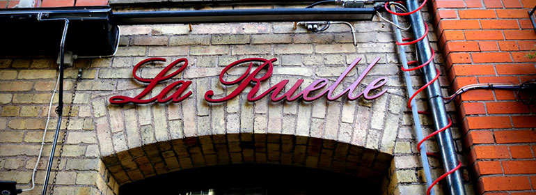 a red sign on a brick wall over an arch saying La Ruelle