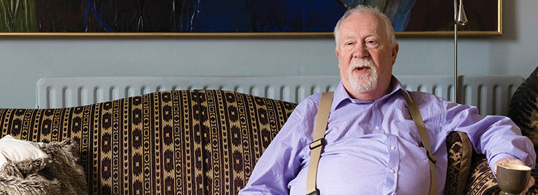 David Parris sitting on a couch with a purple shirt on and suspenders while holding a cup of coffee as he discusses Pension Equality and his former employer Trinity College Dublin, TCD