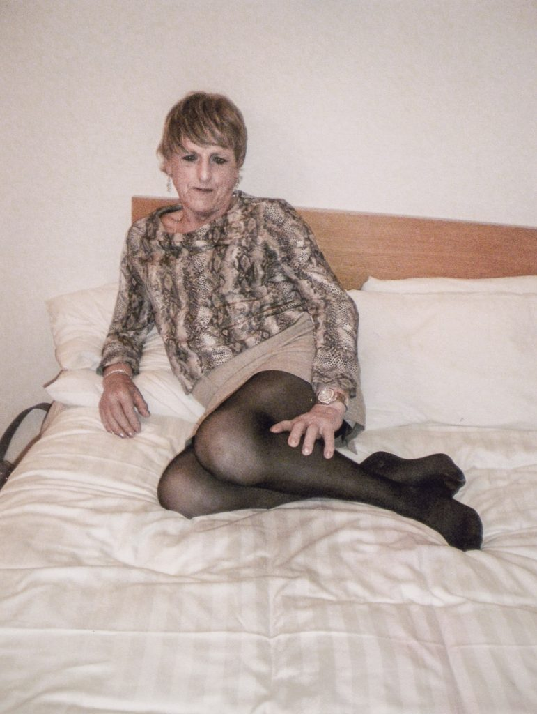 Christine Beynon from the art exhibition in Becoming Christine lying on a bed in with black tights on