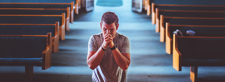 a man kneels in a church of Ireland church praying with his clasped in front of his face