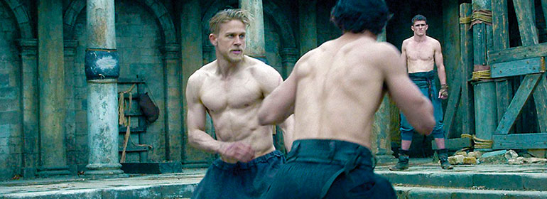 Charlie Hunnam topless fighting another man in Kind Arthur