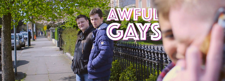 Maurice and Kenny from Awful Gays standing against a railing on a footpath