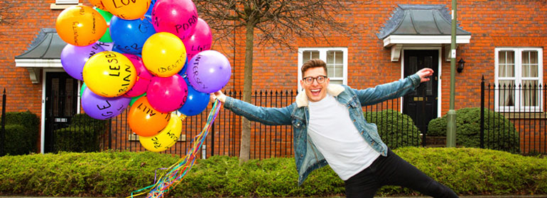 Riyadh K, the presenter of Queer Britain, holding a bunch of balloons in front of a bush and red brick house