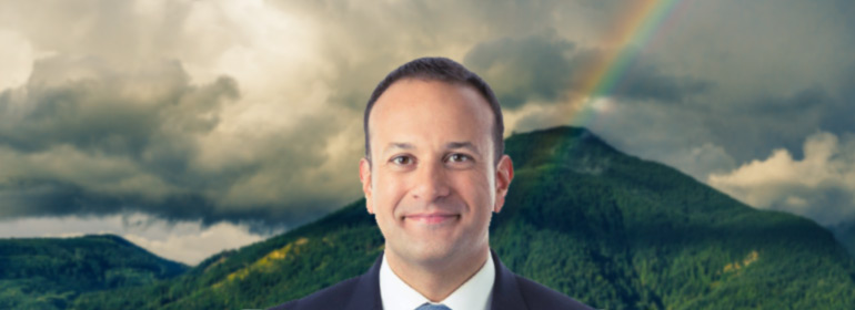 leo varadkar standing in front of a green mountain with a rainbow in the sky