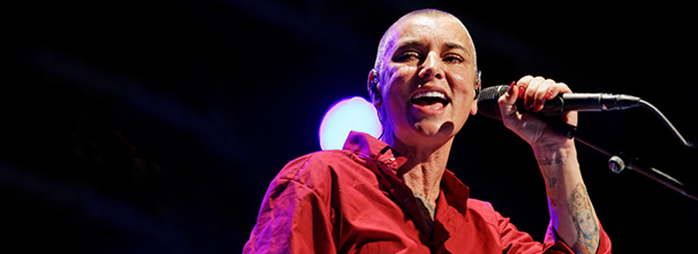 Sinead O'Connor singing in front of a black background, the same woman who plans to give 30 years of gorgeous clothing to trans youth in Ireland