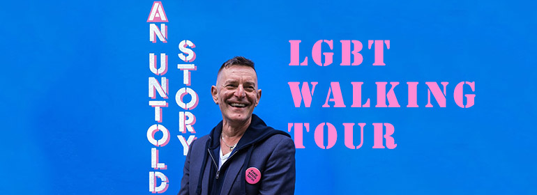 Tonie Walsh against a blue wall with the words an untold story and lgbt walking tour behind him in white and pink, which refer to the tour of gay Dublin Tonie is running