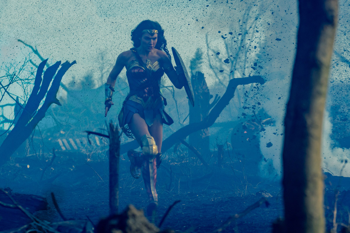 Wonder Woman running through a smokey battlefield