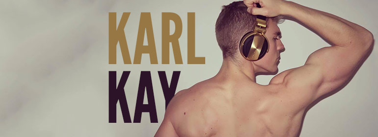 DJ Karl Kay holding his golden headphones without wearing a top