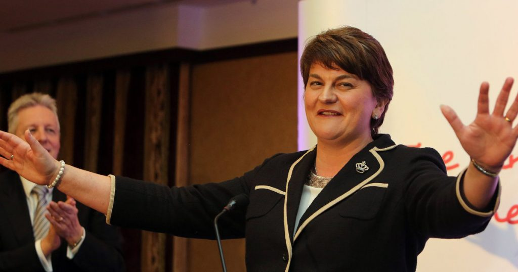DUP leader arlene foster arms spread at a lectern as Peter Robinson looks on