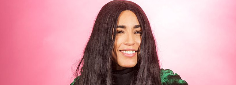 Loreen smiling against a pink background