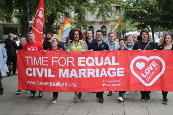 marchers carrying a red banner reading 'time for equal civil marriage'