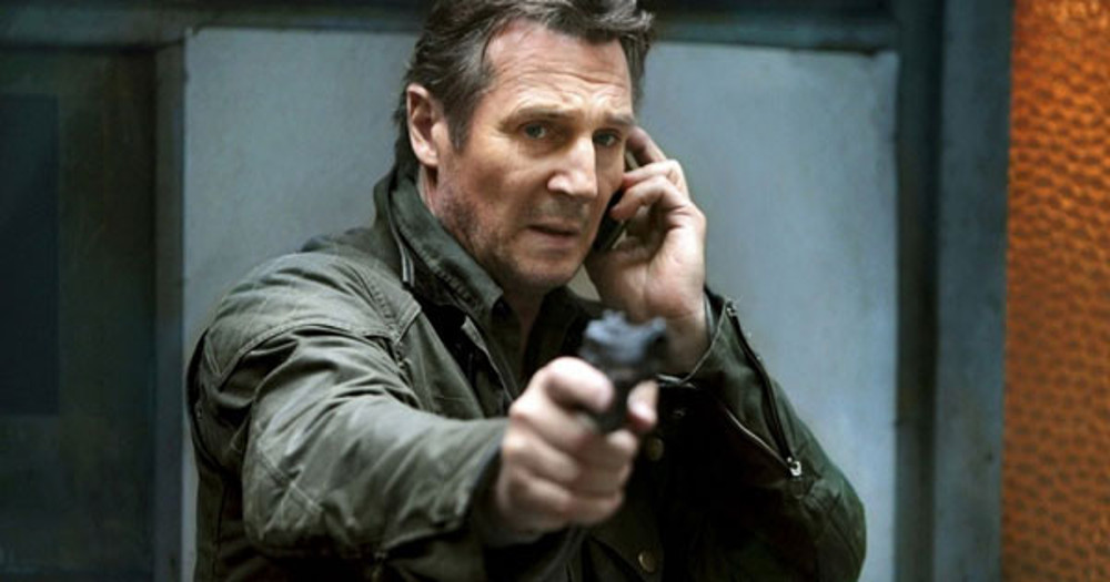 liam neeson points a gun at the camera