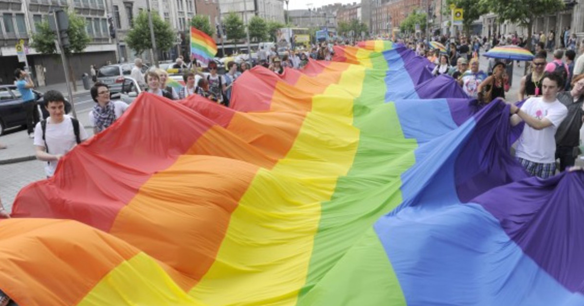 the rainbow flag is carried by an crowd of people down Dublin's O'Connell Street during Pride parade