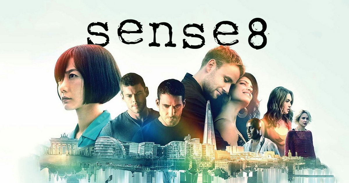 The stars of sense8 standing with the words Sense8 behind them