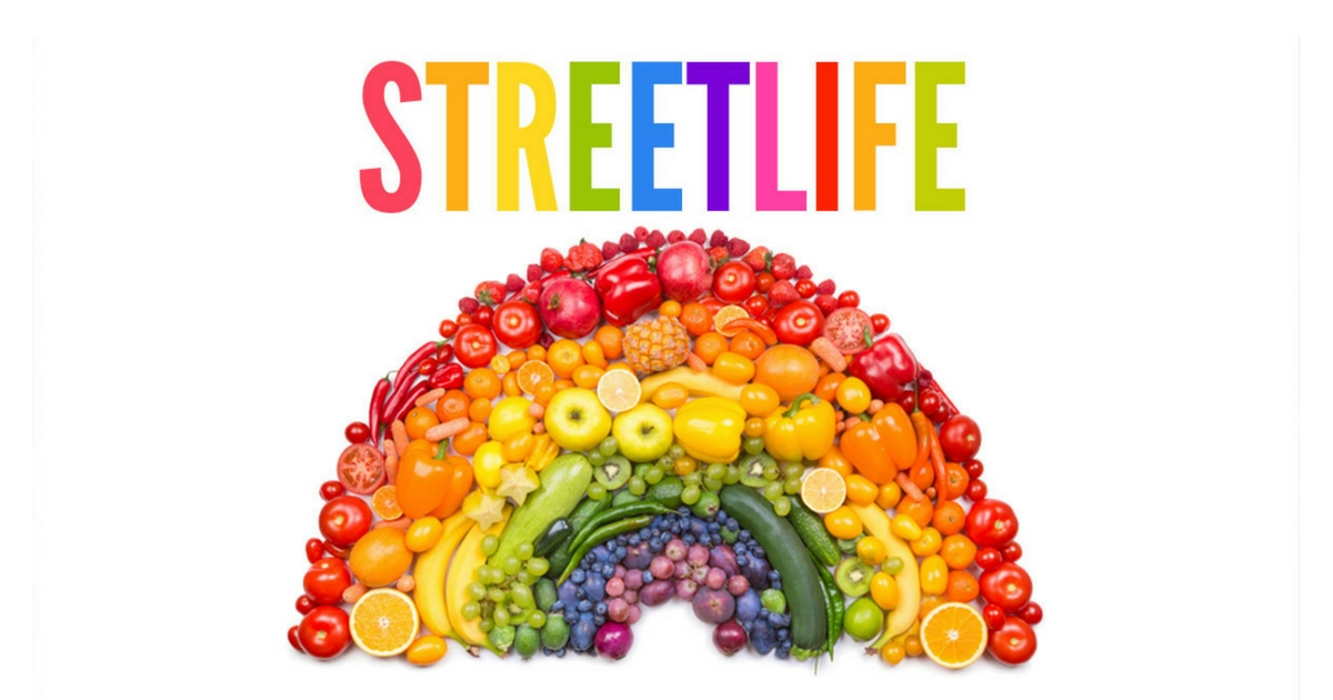 An array of vegetables in the shape and colour of a rainbow with the caption 'Street Life' written above it