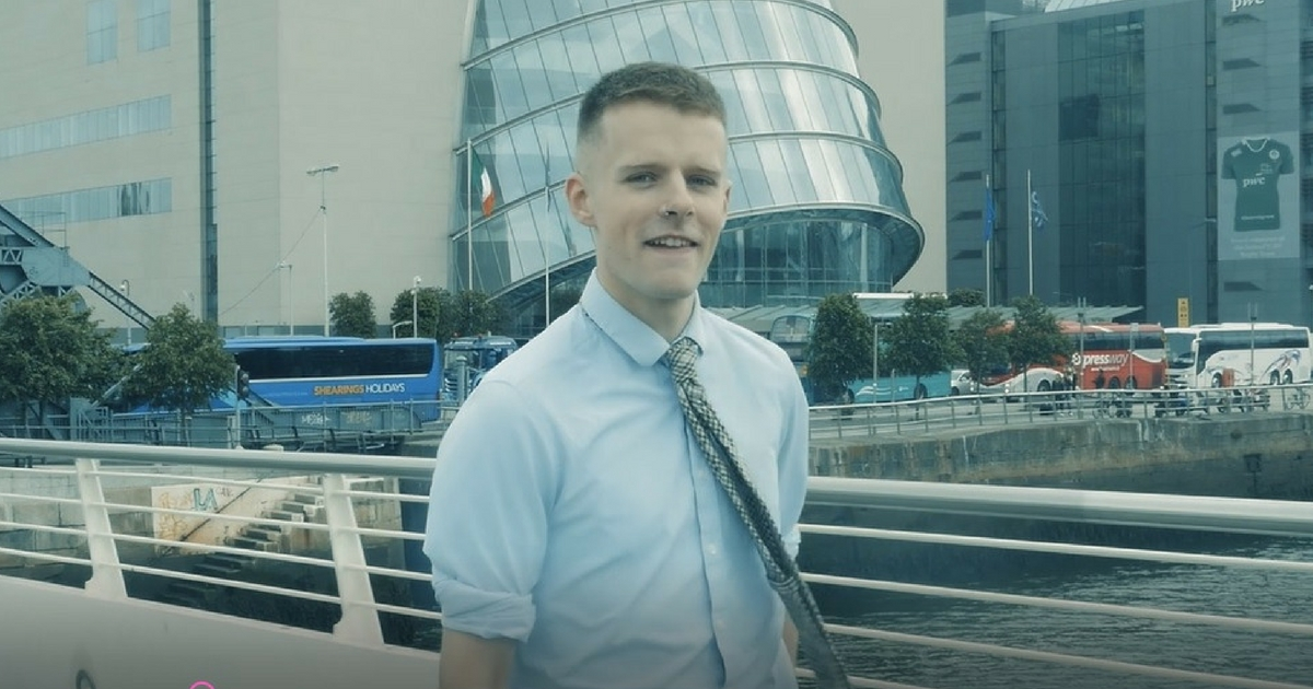 A shot from the newly released video 'Gay, Male, Votes Fine Gael' of Oisin McKenna standing in front of the Dublin Convention Centre performing his poem to camera. He is dressed smartly as a politician, wearing a shirt and tie.