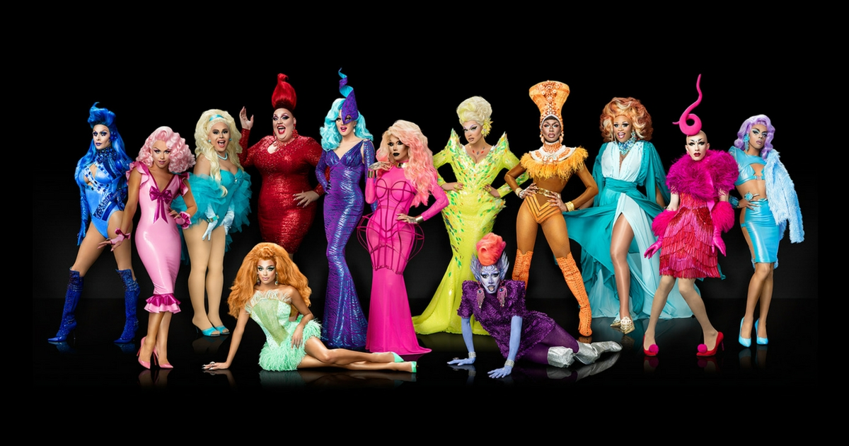 The Drag Queens competing in season 9 of Rupaul's Drag Race pose together in colourful outfits in front of a black back-drop.