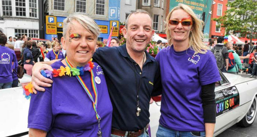 a smiling man is standing in between two woman in purple with his arms around their shoulders