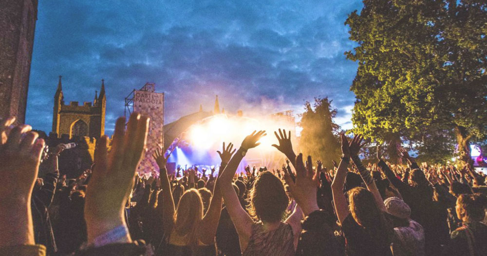 An image of people at Castlepalooza holding their hands up at a concert