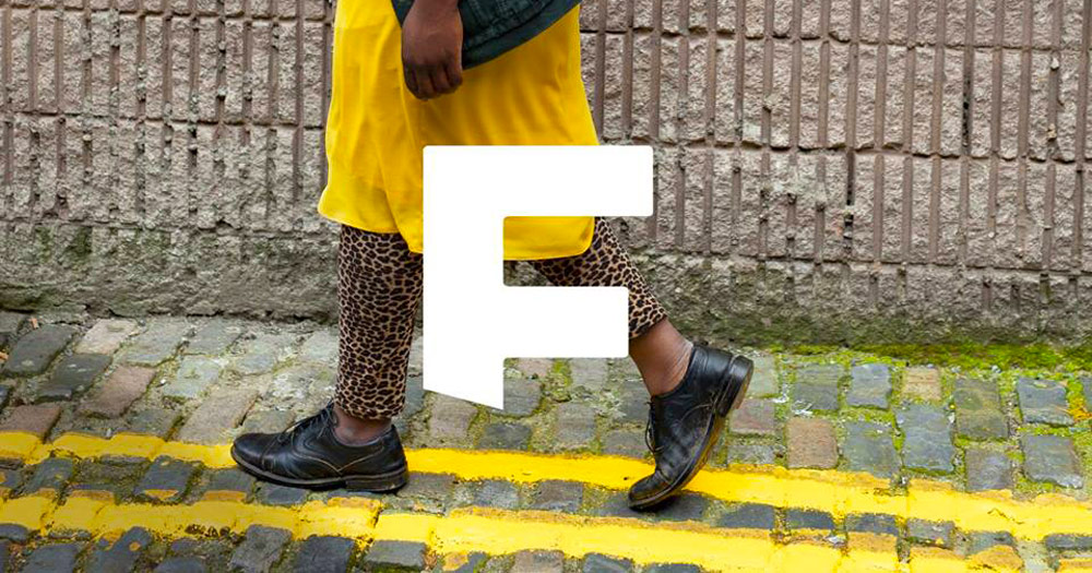 A person wearing a yellow garment and leopard print trousers with an F in front of them for the Dublin Fringe Festival 2017