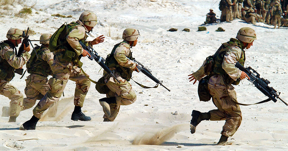 soldiers running on sand with guns in camo suits to represent the irish defence forces who just confirmed they welcome all after Trump's anti-trans tweets