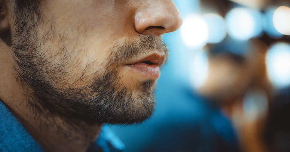A man's face with facial hair to symbolise the one in six asymptomatic men who test positive for an STI