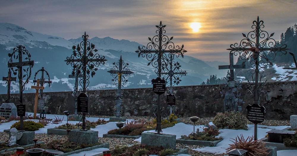 A picture of graves with ornate crosses in front of forests and mountains with the sun peaking out behind some clouds to represent the 27 men murdered in Chechnya