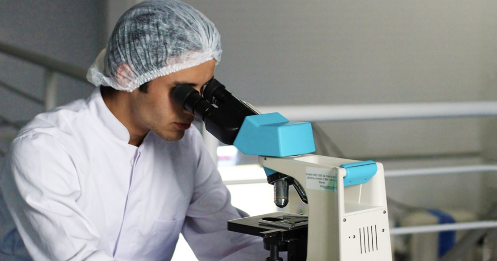 A scientist looking into a microscope to represent the breakthrough in medicine that a gonorrhoea vaccine would symbolise