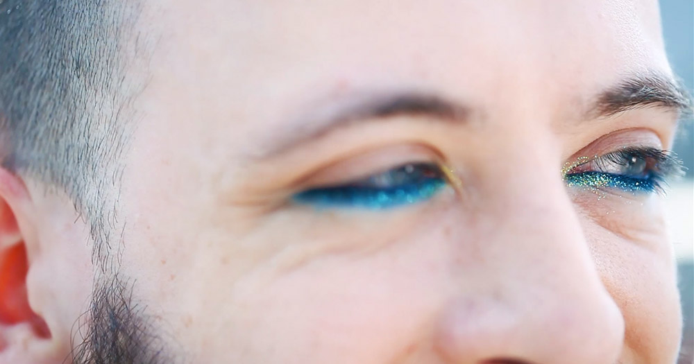 Lorcan Jude Devany's eyes with blue and glittery make-up on while he talks about what pride means to you