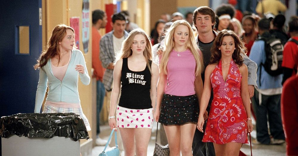 Mean Girls star LiLo and her costars walking down a high school corridor in short skirts