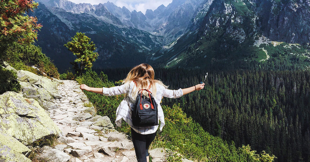 A woman climbing a mountain with her arms spread wide because she's celebrating the annual recovery month from the Rutland Centre