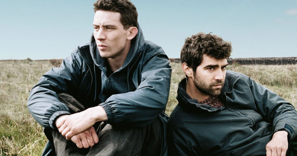 The two characters from God's Own Country sitting in jackets on country grass