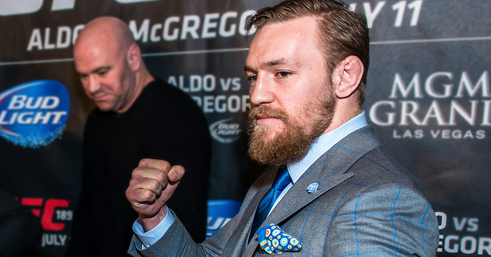 "Conor McGregor, who used the word ""faggot"" as an insult, holding his fist up in a blueish grey suit"