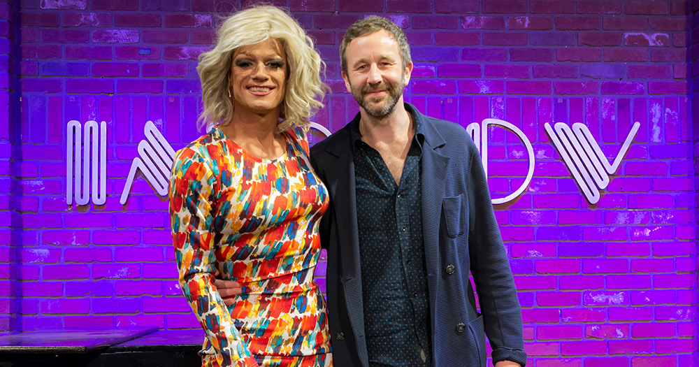 Panti bliss and Chris O'Down at Ireland week standing in front of a brick wall that says (Hollywood) improv