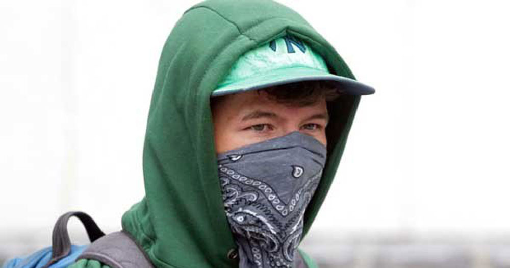 A guy wearing a green hat, a hoodie and a headscarf to cover his face