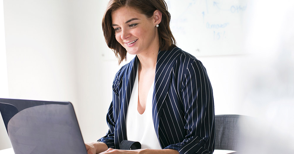 A woman smiling as she takes part in the mental health survey on the laptop she's typing on at her desk