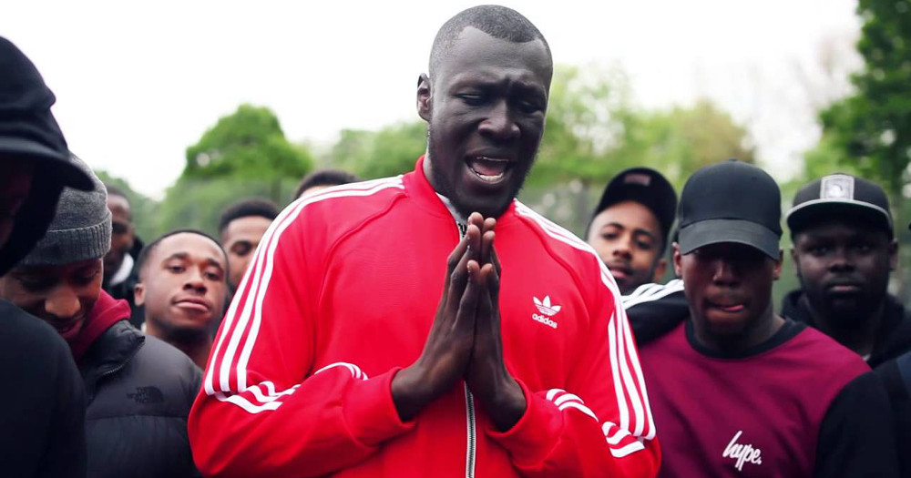 Black grime artist Stormzy, hands together in prayer, wearing a red Adidas top