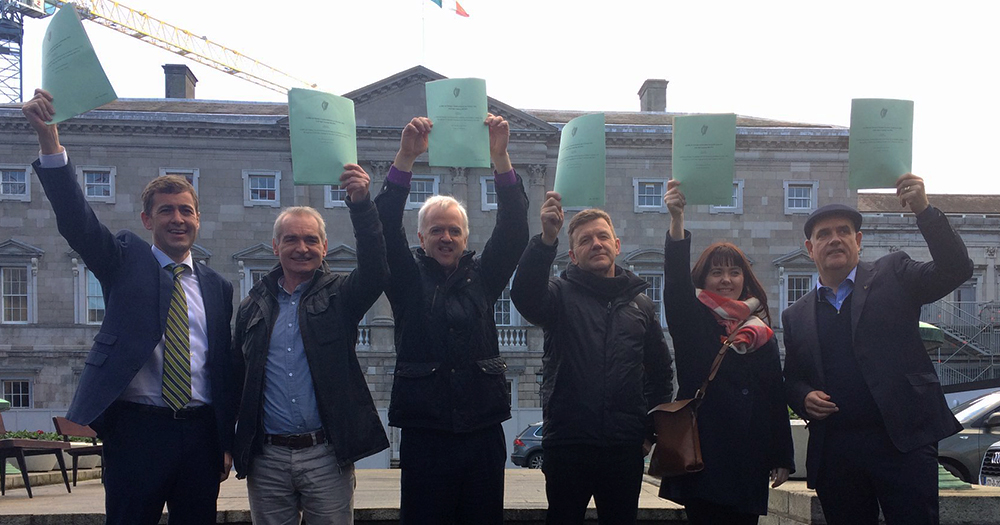 Memebers of the deaf community hold the bill up outside the Dail