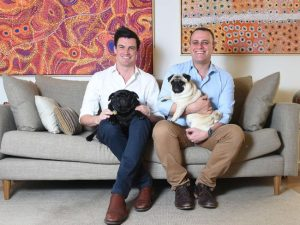 Photo of Ryan Bolger and Tim Wilson in their home with their two pet pugs