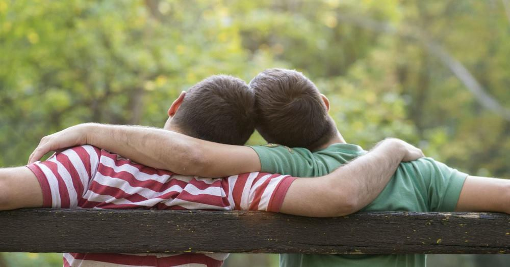 Two guys on sitting a bench hugging each other