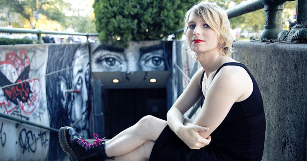 Chelsea Manning sits on a wall with graffiti in the background