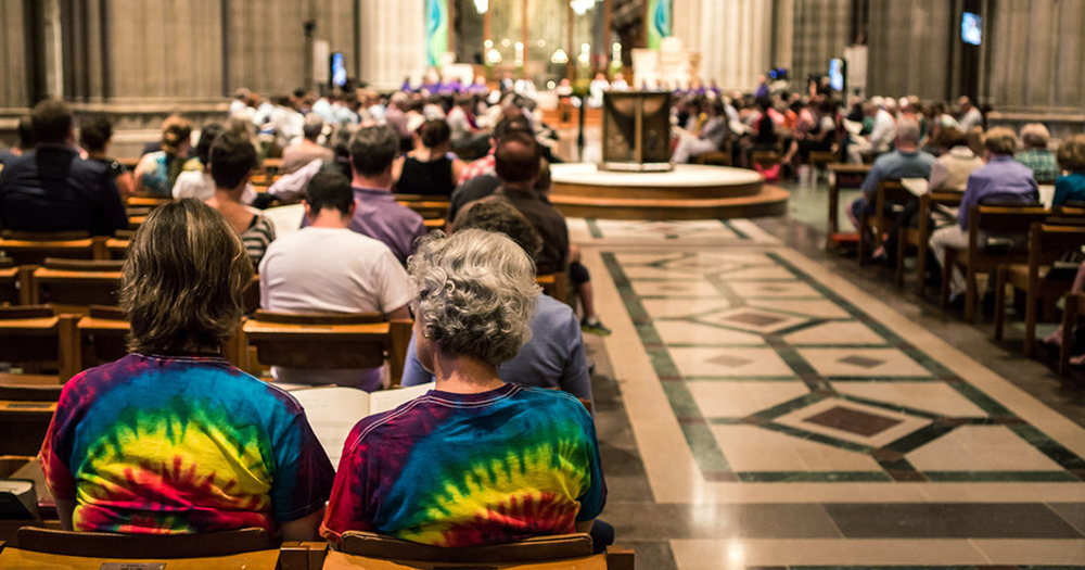 Couple sit in a church wearing tie dye t-shirts